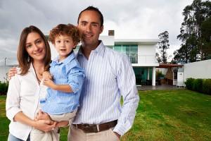 Junge Familie steht von einem Haus