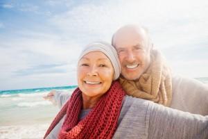 Rentnerpaar hat sich umarmt am Strand