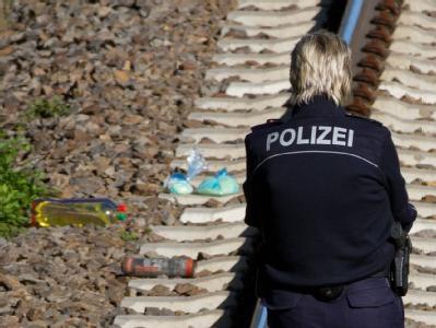 Eine Polizeibeamtin nahe des Bahnhofes Südkreuz in Berlin an einer Bahnstrecke. Hier wurde einer der Brandsätze entdeckt. Foto: Herbert Knosowski