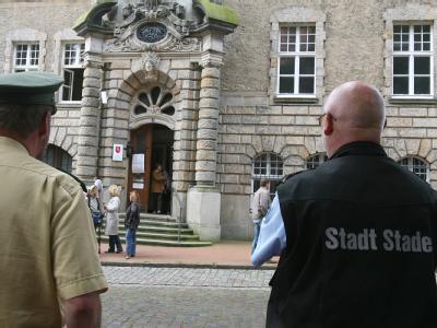 Ein Polizist und ein Mitarbeiter des Ordnungsamtes vor dem Landgericht in Stade. (Archiv- und Symbolbild)