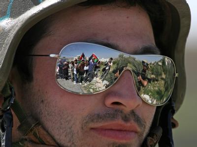 Palästinenser spiegeln sich in der Sonnenbrille eines israelischen Soldaten.