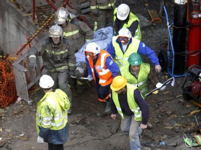 Rettungskräfte bringen ein Opfer des Tunneleinsturzes vom Unglücksort.