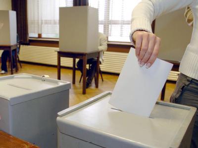 Eine Wählerin steckt bei einer Kommunalwahl ihre Stimmzettel in die Wahlurne.