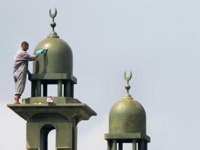 Ein Arbeiter putzt ein Minarett am Neubau einer Moschee. (Archivbild)