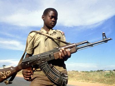 Ein Kindersoldat posiert in Uganda mit seiner Waffe (Symbol- und Archivfoto). Der internationale Waffenhandel soll stärker reglementiert werden.