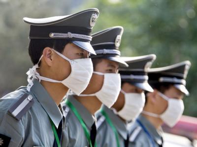 Chinesische Sicherheitskräfte versuchen sich vor einer Ansteckung mit der Schweinegrippe zu schützen.