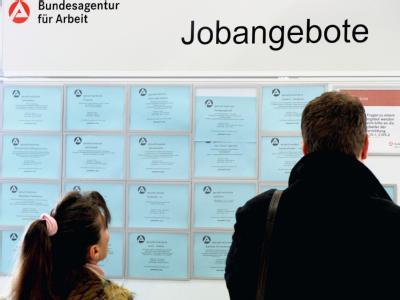 Beim Tag der Zeitarbeit suchen Bewerber an einer Informationstafel nach offenen Stellen. Foto: Martin Schutt/Archiv