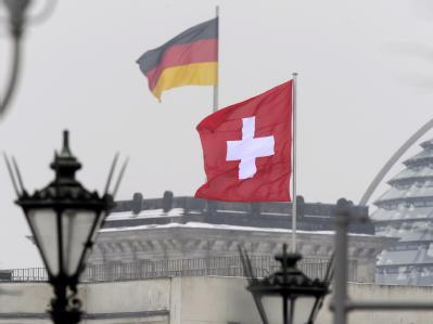 Die Schweizer Flagge auf dem Dach der Schweizer Botschaft in der Nähe zur Glaskuppel des Bundestages. Foto: Rainer Jensen