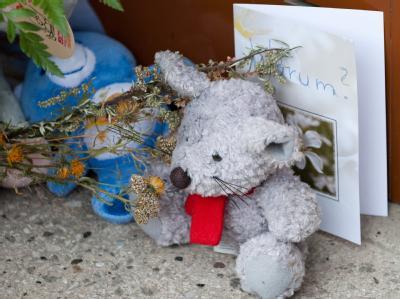 Kerzen, Blumen und Plüschtiere erinnern vor einem Hauseingang an ein getötetes Kleinkind.