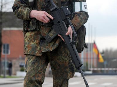 Ein Soldat der Bundeswehr vor dem Haupttor einer Kaserne.