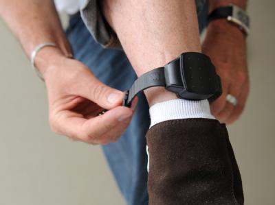 Ein Bewährungshelfer demonstriert den Einsatz einer elektronische Fußfessel.