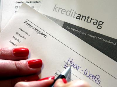 Eine Frau füllt einen Kreditantrag für einen Unternehmenskredit aus. Foto: Oliver Berg/Symbolbild