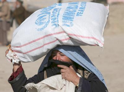 Eine Afghanin trägt einen Sack mit Lebensmitteln des UN-Flüchtlingskommissariats UNHCR.
