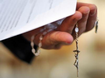 Ein Priester hält einen Rosenkranz und eine bischöfliche Erklärung zu den Missbrauchsfällen durch Jesuiten-Pater in der Hand. (Archivbild)