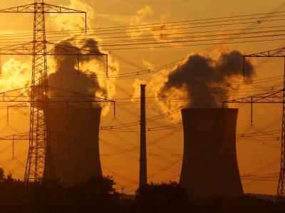 Das Licht der untergehenden Sonne fällt auf die Kühltürme eines Atomkraftwerks.