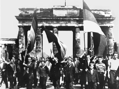 Ost-Berliner ziehen am 17.6.1953 mit wehenden Fahnen vom Ost-Sektor aus durch das Brandenburger Tor.