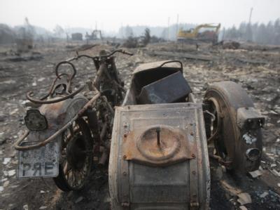 Ein ausgebranntes Motorrad in einem zerstörten russischen Dorf.