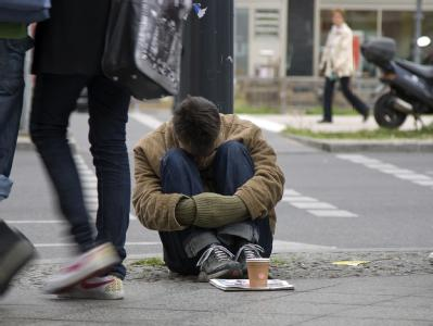 Ein Obdachloser bettelt an einem Fußgängerüberweg in Berlin um Geld. (Archiv- und Symbolbild)