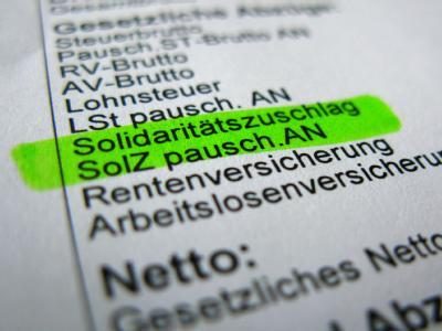Der «Soli» wird bis auf weiteres auch künftig auf den Lohnabrechnungen erscheinen.