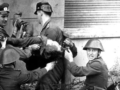 Grenzposten tragen 1962 in Berlin den leblosen Körper von Peter Fechter weg. Der angeschossene 18-Jährige hatte vor seinem Tod eine gute Stunde um Hilfe gerufen, ohne dass die Grenzer ihm halfen.