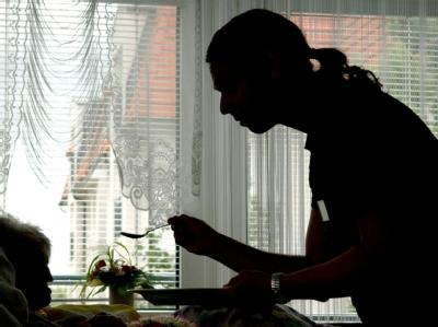 Ein Zivildienstleistender füttert in einem Seniorenzentrum eine Heimbewohnerin. (Archivbild)