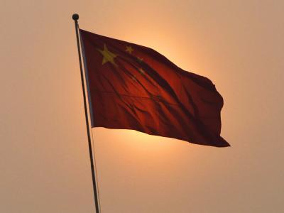 Die chinesische Flagge im Licht der aufgehenden Sonne. Foto: How Hwee Young