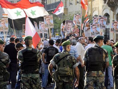 Polizisten und Assad-Anhänger bei einer Demo in Beirut. Zur libanesischen Regierung gehört die mit Damaskus kooperierende Hisbollah-Bewegung. Foto: Wael Hamzeh