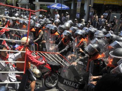 Anhänger der Opposition versuchen durch eine Absperrung der Polizei zu brechen.