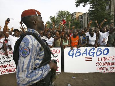 Ein bewaffneter ivorischer Polizist beobachtet eine Demonstration von Gbagbo-Anhängern.