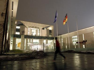 Ein Jogger vor dem hell erleuchteten Bundeskanzleramt in Berlin.