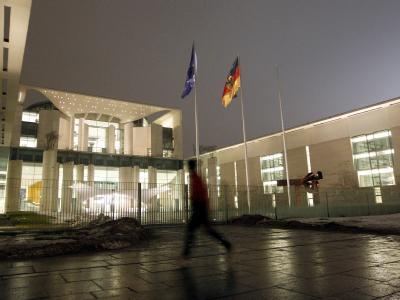 Ein Jogger läuft am hell erleuchteten Bundeskanzleramt in Berlin vorbei.