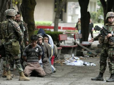 Soldaten mit festgenommenen Plünderern in Talcahuano.