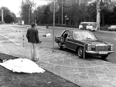 April 1977: Der Tatort mit der zugedeckten Leichen von Siegfried Buback (vorne links). Mit ihm starben sein Fahrer (43) und der 30-jährige Leiter der Fahrbereitschaft.