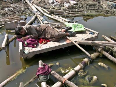 Ein Pakistaner schläft im Flutgebiet auf den Trümmern seines zerstörten Hauses.