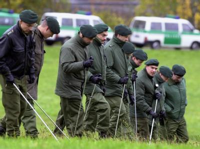 Polizeibeamte suchen im Oktober 2000 eine Wiese bei Weil im Schönbuch ab. Einen Tag zuvor war in der Nähe die Leiche des elfjährigen Schülers gefunden worden.