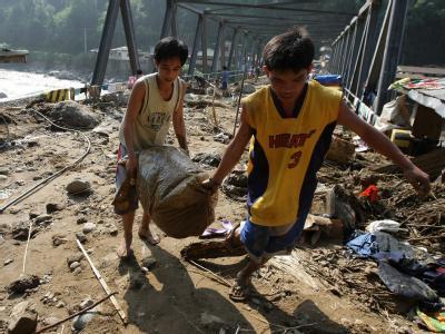 Zwei Jungen haben in den Trümmern ihres Hauses verwertbare Gegenstände zusammengesucht.