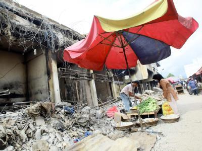 Vor den Trümmern eines zerstörten Hauses in Padang hat ein Mann einen provisorischen Marktstand errichtet.