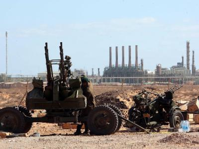 Ein Geschütz der Gaddafi-Gegner vor der Kulisse der Öl-Raffinerie von Ras Lanuf.