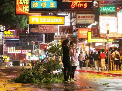 Fußgänger in einer Straße von Hongkong neben einem vom Sturm umgerissenen Baum.