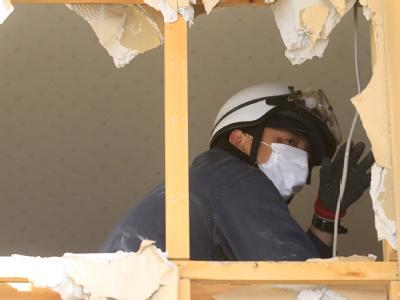 Ein Polizist durchsucht die Trümmer eines von Beben und Tsunami zerstörten Hauses.