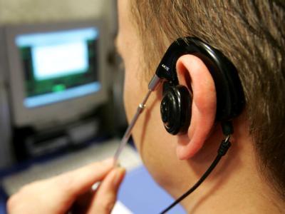 Ein Call-Center-Mitarbeiter an seinem Arbeitsplatz. Verbraucher werden künftig besser vor lästiger Telefonwerbung geschützt.