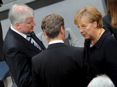 Horst Seehofer (CSU), Guido Westerwelle (FDP) und Kanzlerin Merkel (CDU) bei einem Gespräch im Bundestag.