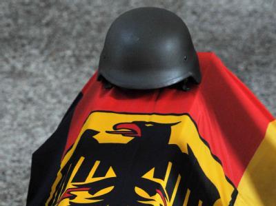 Ein Stahlhelm liegt auf dem mit der deutschen Flagge bedeckten Sarg eines Bundeswehr-Soldaten, der im Juni 2009 in Afghanistan ums Leben kam.