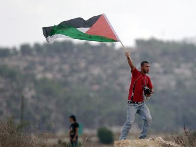 Ein Palästinenser schwenkt im Westjordanland eine Fahne mit den Farben der Palästinenser.