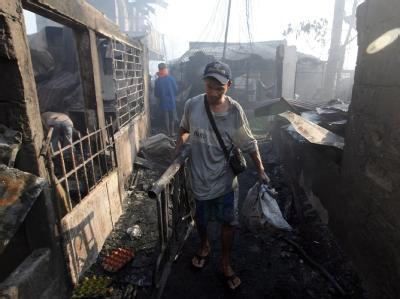 Ein Mann rettet nach dem Brand verwertbare Dinge aus den Trümmern.