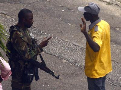 Ein Gbagbo-treuer Soldat befragt in einer Straße in Abidjan einen Zivilisten.