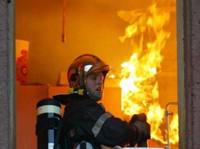 Ein Feuerwehrmann am Fenster eines brennenden Hauses. (Archiv- und Symbolbild)