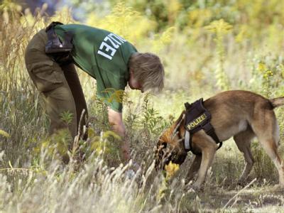 Ein Polizist durchsucht im Herbst 2009 mit einem Hund das Gelände eines ehemaligen Güterbahnhofs in Berlin.
