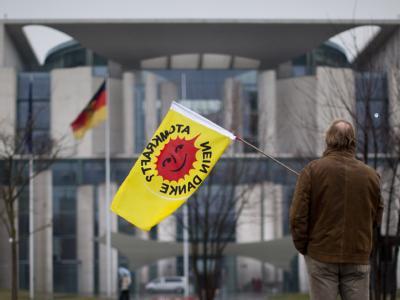 Ein einsamer Demonstrant steht mit einer Flagge der Atomkraftgegner vor dem Kanzleramt in Berlin. (Archivbild)