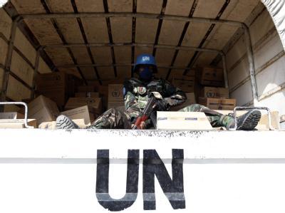 Ein Blauhelm-Soldat bewacht ein Fahrzeug der Vereinten Nationen.